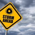 """Photo of cloudy sky with a yellow sign that reads """"Storm Ahead""""."""