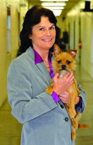 Photo of Kim Staton, Director of Osceola County Animal Services holding small dog.